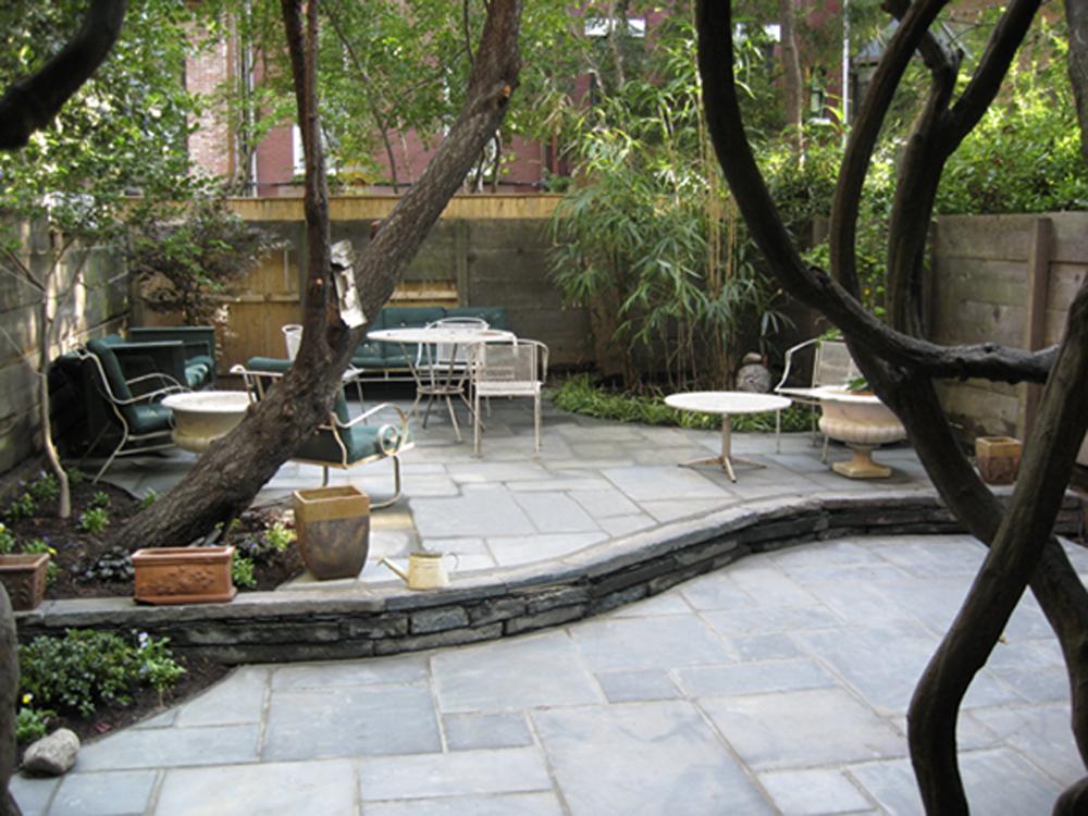Hardscape patio construction of a bluestone backyard patio, custom stonework and masonry.